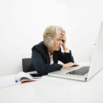 Stressed senior businesswoman using laptop at desk in office